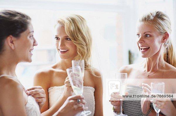 Bride and bridesmaids toasting and talking