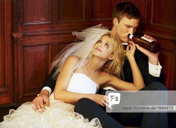 Drunk bride and groom sitting on floor
