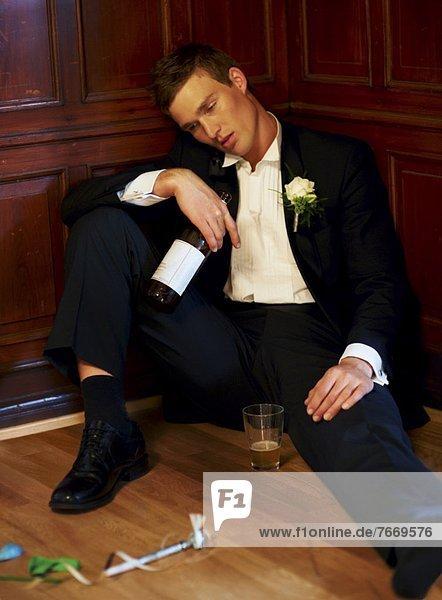 Drunk groom sitting on floor