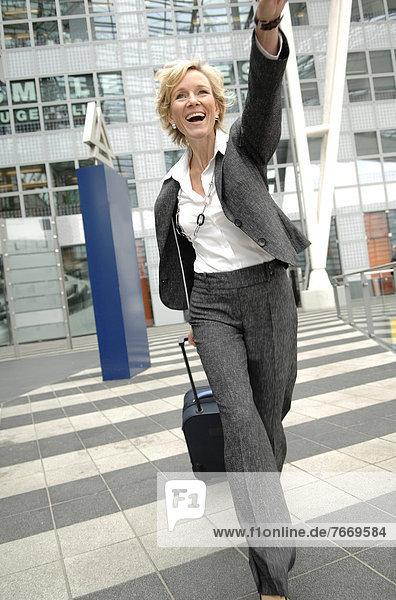 Geschäftsfrau  40-50 Jahre  mit Rollkoffer  winkt
