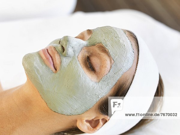 Woman with face mask relaxing in spa