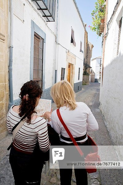 Two tourists look at a map of the city of Ubeda  province of Jaen  Spain