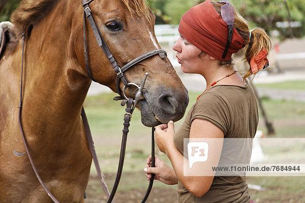 Eine Frau beruhigt ihr Pferd Eine Frau beruhigt ihr Pferd