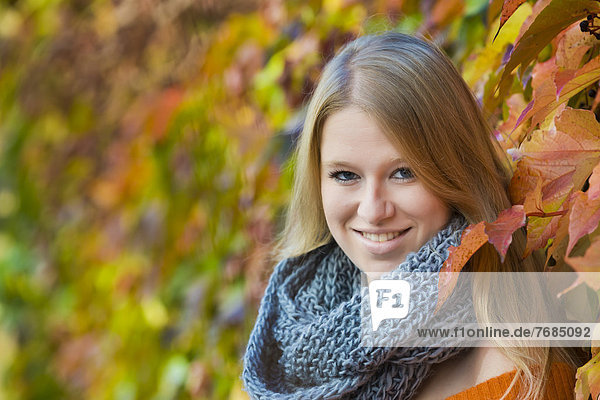 Young woman wearing a thick scarf in front of colourful autumn leaves