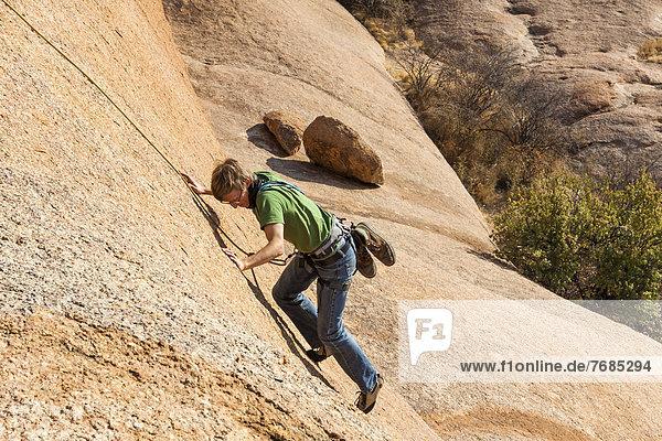 Junger Mann beim Klettern am Bogenfels  Spitkoppe-Gebiet  Damaraland  Namibia  Afrika