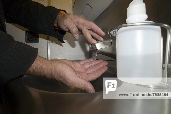 A passenger washing his hands in the lavatory of an airplane  Boeing 777