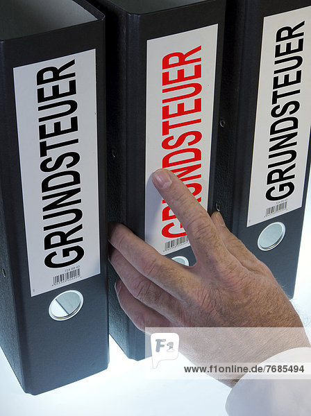 'Hand reaching for file folders labeled ''Grundsteuer''  German for ''land tax'''