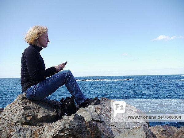 Frau mit Smartphone sitzt auf einem Felsen und schaut aufs Meer  in Roque de las Bodegas  Teneriffa  Kanarische Inseln  Spanien  Europa