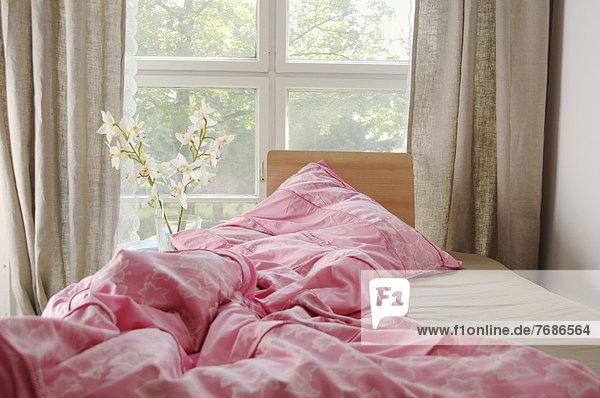 Bett am Fenster mit zerwühlter pinker Bettdecke