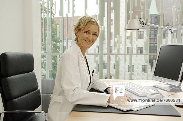 Ärztin im weißen Kittel sitzt am Schreibtisch