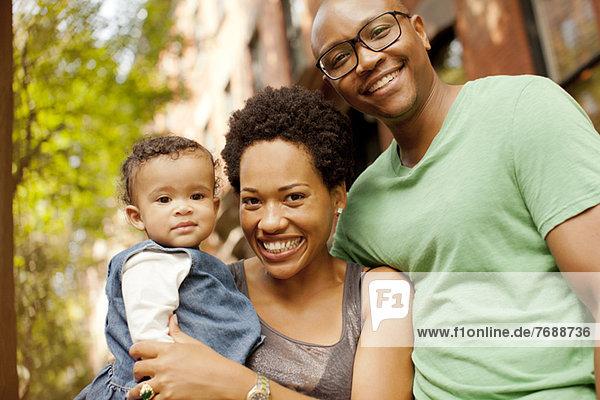 Lächelnde Familie steht im Freien