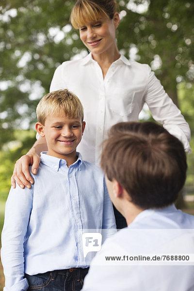 Mutter  Vater und Sohn im Park im Gespräch