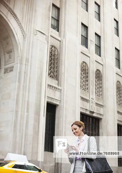 Geschäftsfrau mit Tablet-Computer auf der Stadtstraße