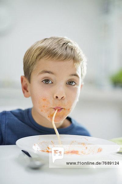 Jungen schlürfen Spaghetti bei Tisch