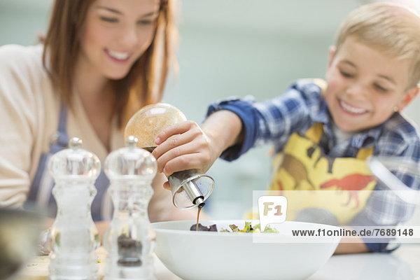 Mutter und Sohn machen Salat in der Küche Mutter und Sohn machen Salat in der Küche