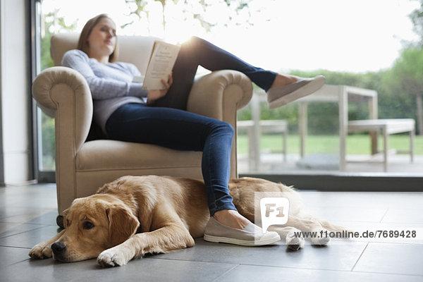 Hund sitzend mit Frau im Wohnzimmer