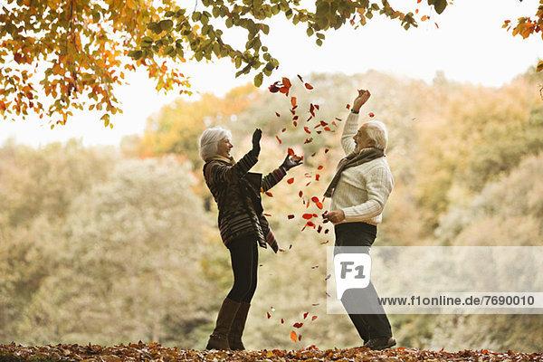 Älteres Paar spielt im Herbstlaub