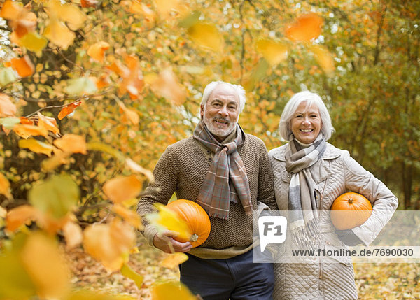 Älteres Paar mit Kürbissen im Park Älteres Paar mit Kürbissen im Park