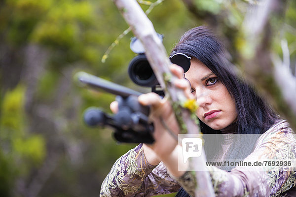 USA  Texas  Young woman with hunting rifle  close up