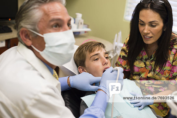 Dentist and nurse examining patient's mouth