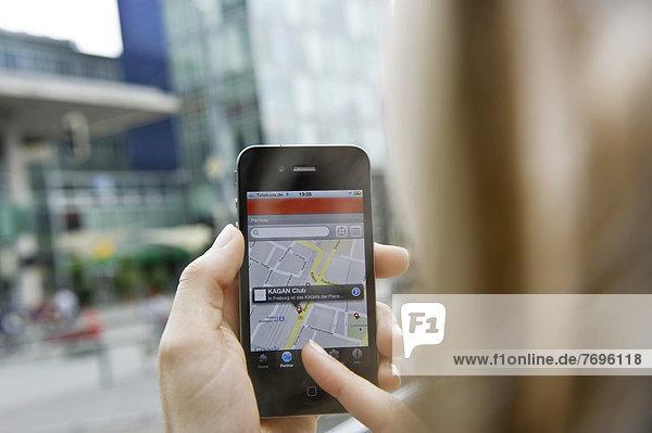 Junge Frau navigiert mit Smartphone