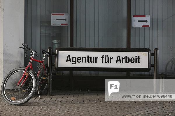 'Fahrrad geparkt neben Schild ''Agentur für Arbeit'''