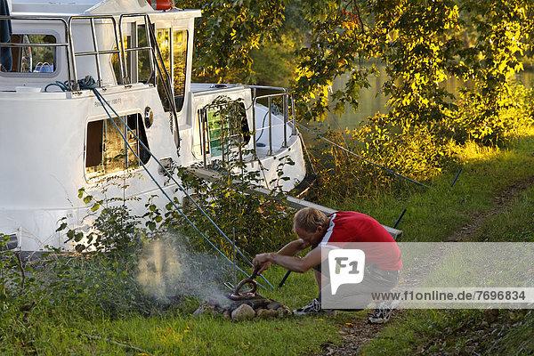 Mann macht Grillfeuer fürs Abendessen  neben Hausboot auf dem Canal du Midi  bei Écluse de l'Ocean  Pk 51 6