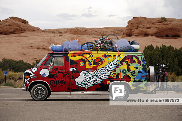 Buntbemalter beladener Kleinbusvor Felslandschaft  Utah  USA
