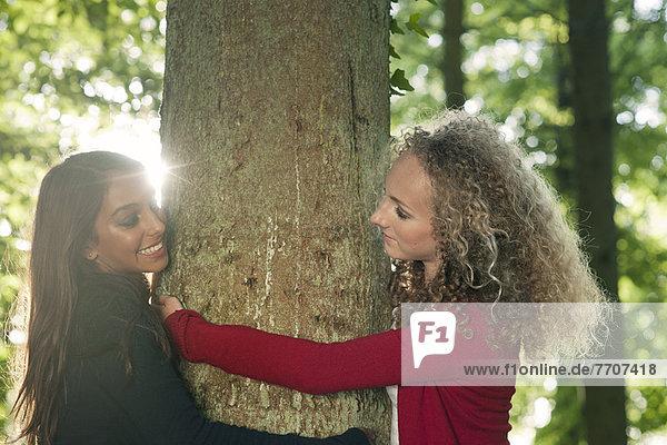 Teenagermädchen umarmen Baum im Wald