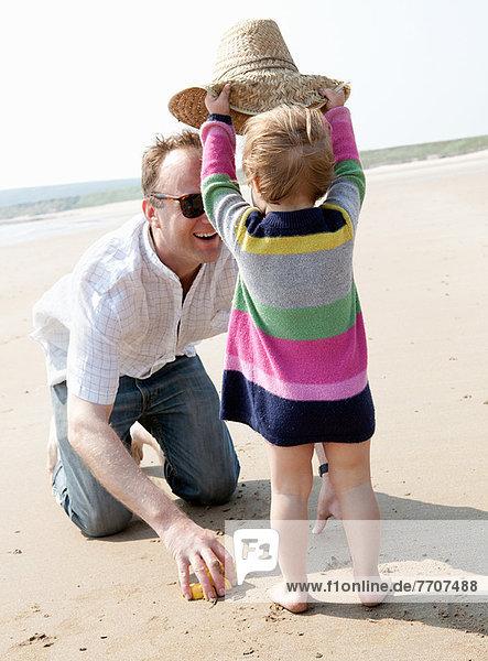 Mädchen mit Hut auf Vater am Strand