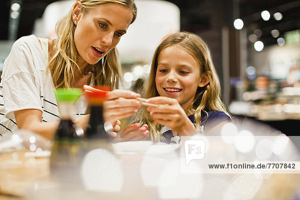 Mother and daughter using chopsticks