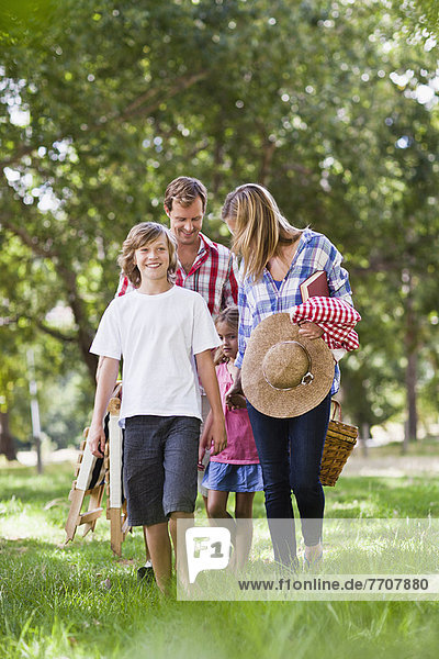 Family with picnic basket in park