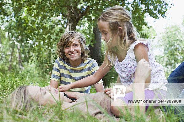 Mutter und Kinder beim Spielen im Park