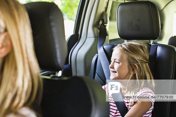 Mädchen lächelnd auf dem Rücksitz des Autos