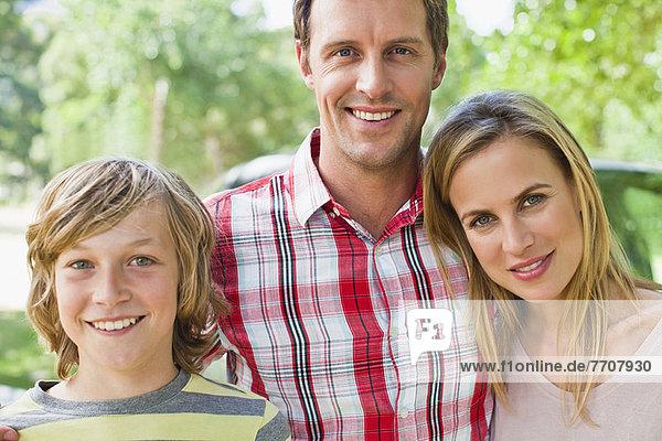 Familie lächelt zusammen mit dem Auto