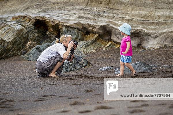 Mutter fotografiert Tochter am Strand