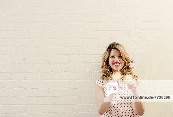 Lächelnde Frau hält Wunderkerzen.