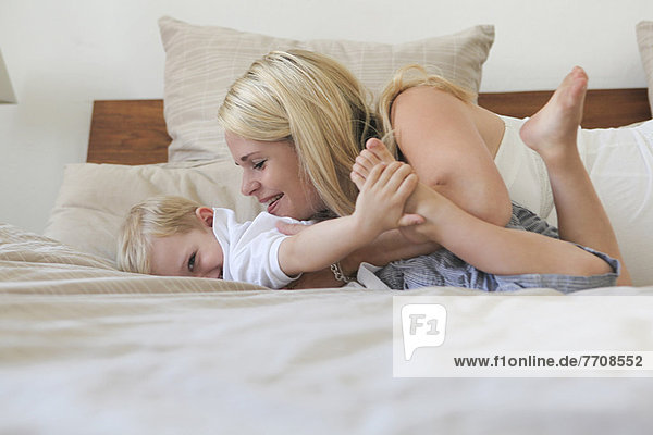 Mutter und Sohn spielen auf dem Bett