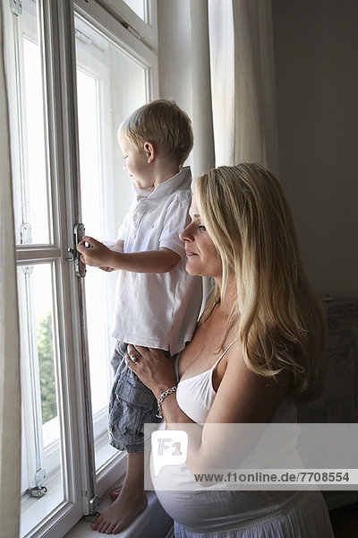 Schwangere Mutter und Sohn am Fenster