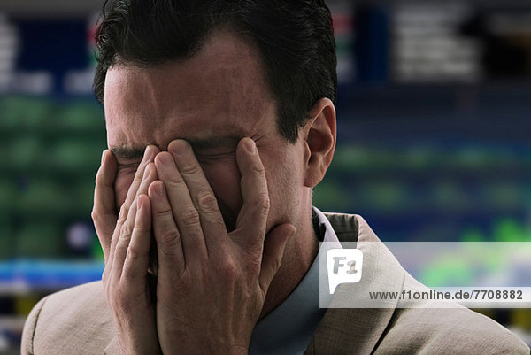 Businessman crying at stock exchange