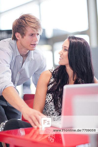 Paar mit Laptop zusammen am Schreibtisch