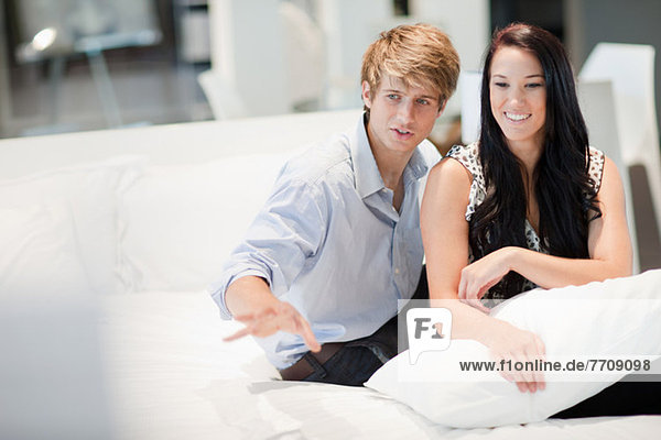 Couple shopping for mattress in store