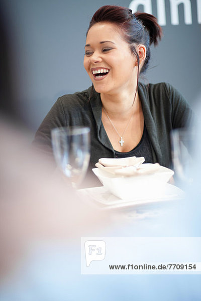 Woman laughing at dinner table