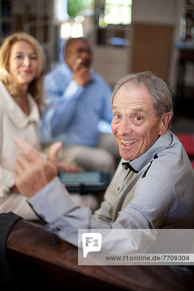 Older man smiling in armchair