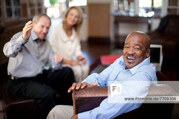 Älterer Mann lächelt im Sessel