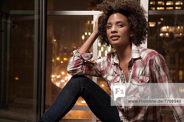 Frau auf der Fensterbank sitzend
