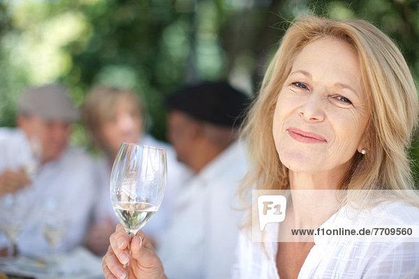 Ältere Frau mit Wein im Freien