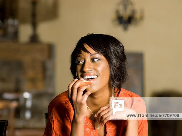 Woman eating fruit indoors