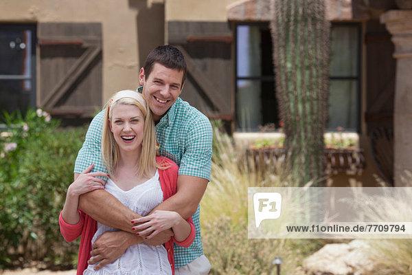 Lächelndes Paar  das sich im Freien umarmt.