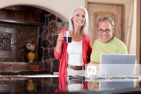 Älteres Paar mit Laptop beim Frühstück